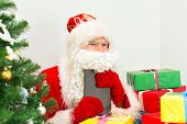 Santa Claus Checking Wish List At His Workshop.