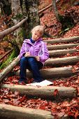 image of gril  - Little artist gril with sketch in note at autumn landscape - JPG