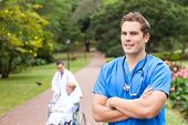 stock photo of physical therapist  - young intern outdoors with patient and doctor in background - JPG