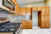 Luxury Kitchen Room With Bright Brown Cabinets And Mosaic Wall Trim