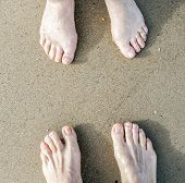 Feet Of A Couple At The Beach