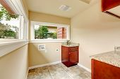 pic of laundry  - Soft tones laundry room wtih tile floor and cabinets - JPG