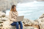 Beautiful Woman Browsing Her Laptop In Winter On The Coast