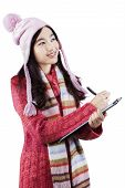 Girl Wearing Warm Clothes And Writes On Clipboard