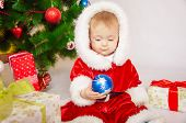 Baby in Santa costume at the Christmas tree
