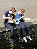 Teenagers eating fish and chips.