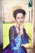 Beautiful Medieval Woman In Blue Dress Making Silence Gesture