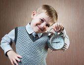 stock photo of diligent  - Portrait of cute diligent boy holding alarm clock - JPG