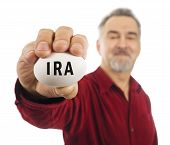 Mature Man Holds White Nest Egg With IRA On It.