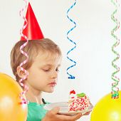 Little child in holiday hat eating birthday cake