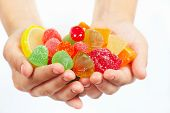 Child hands with colorful sweetmeats and jelly close up