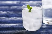 Glass with ice cubes on wooden table