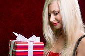 Portrait Of Casual Young Happy Blonde Hold Striped Gift Box
