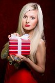 Portrait Of Casual Young Happy Smiling Blonde Hold Striped Gift Box