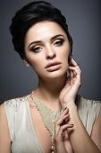 Beautiful brunette woman with perfect skin, gold makeup and handmade jewelry. Beauty face.