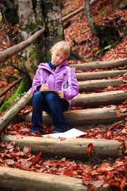 stock photo of grils  - Little artist gril with sketch in note at autumn landscape - JPG