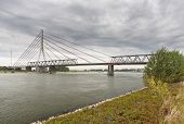 picture of old bridge  - Deconstruction of an old bridge over Rhine river next to a new suspension bridge in Wesel Germany - JPG
