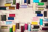pic of lurex  - bobbins with colorful threads on old wooden table - JPG