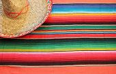 foto of mexican fiesta  - fiesta mexican poncho rug in bright colors with sombrero background with copy space cinco de mayo - JPG