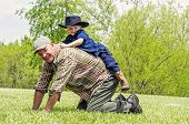 image of grandpa  - Young child gets a horsey ride on his grandpa