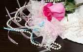 foto of garter  - Beautiful pink rose pearl beads and white stockings with garter lying on a table - JPG