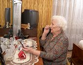 pic of face-powder  - Senior caucasian woman about ninety years old puts on face powder before the mirror in her bed room - JPG