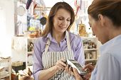stock photo of debit card  - Customer Paying In Kitchen Shop Using Credit Card Terminal