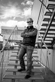 stock photo of staircases  - Black and white photo of young male architect standing on metal staircase - JPG