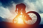 image of mountain-high  - Man riding a bike in high mountains at sunset - JPG