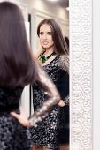 foto of evening gown  - Portrait of a young woman in a dressing room with an evening gown and a statement necklace - JPG