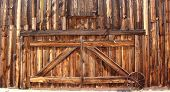 image of wagon  - Front entrance of an old wooden farmhouse barn doors with metal wagon wheel - JPG