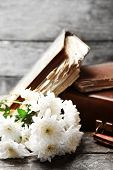 stock photo of old suitcase  - Old wooden suitcase with old books and flowers on wooden background - JPG