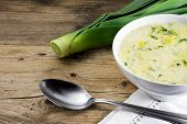 picture of leek  - vegetable cream soup in a white ceramic bowl spoon and fresh leek on rustic wood - JPG