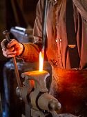 stock photo of blacksmith shop  - Blacksmith hammering a hot metal rod on an anvil - JPG