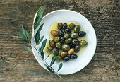 stock photo of olive trees  - A plate of Mediterranean olives in olive oil with a branch of olive tree over a rough old wooden desk - JPG