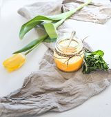 stock photo of curd  - Lemon curd in a jar bunch of fresh mint and yellow tulip over rustic dark backdrop - JPG
