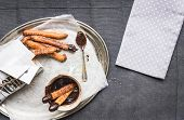 foto of churros  - Churros with chocolate sauce on a metal plate over a linen table cloth - JPG