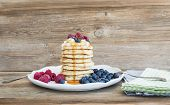 picture of maple syrup  - Pancakes with creamy cheese topping garden berries and maple syrup over a rustic wooden background - JPG