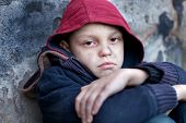 foto of homeless  - homeless young boy leaned against the wall - JPG