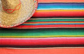 stock photo of mexican fiesta  - fiesta mexican poncho rug in bright colors with sombrero background with copy space cinco de mayo - JPG