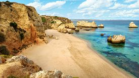 foto of atlantic ocean  - Scenic beach paradise at the Atlantic with the clear blue green water of the ocean and high cliffs with warm colors - JPG