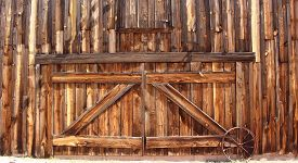 pic of wagon  - Front entrance of an old wooden farmhouse barn doors with metal wagon wheel - JPG
