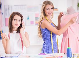 stock photo of dress mannequin  - Blond hair woman working at pink dress on mannequin and brown hair woman speaking by phone in studio - JPG