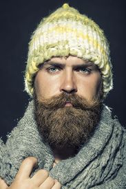 picture of long beard  - Portrait of unsocial unshaven hobo man with long beard and handlebar mustache in knitted yellow hat and grey scarf looking forward on black background - JPG