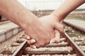 Couple walk, hand by hand, along railroad