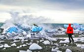 Woman Watching Waves Crash Against Icebergs At Jokulsarlon Glacial Lagoon Near Vatnajokull National poster