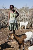 African woman with braids dressed in colorful clothes standing in the kraal