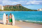Hawaii surf couple on waikiki beach in Honolulu, Hawaii. Summer holidays travel destination young pe poster