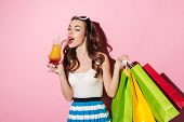 Постер, плакат: Portrait of a beautiful young girl shopaholic drinking cocktail and holding colorful shopping bags i