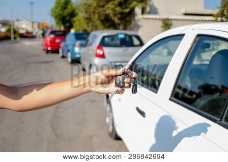poster of Woman Getting Her Key In The Car. Concept Of Rent Car Or Buying Car.travel Vacation With Rental Car.
